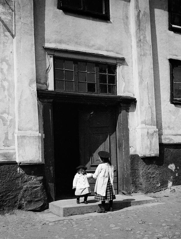 Två barn står vid porten på gårdssidan av Värmdögatan 63.